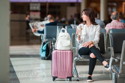 Young woman with coffee in an airport lounge waiting for flight aircraft