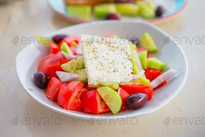Delicious fresh greek salad served for lunch at outdoor restaurant with beautiful view on the sea
