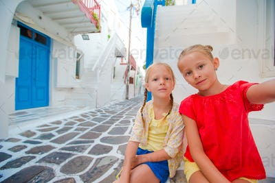 Two girls taking selfie photo outdoors in greek village on narrow street