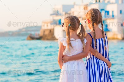 Back view of little kids at Little Venice the most popular tourist area on Mykonos island, Greece