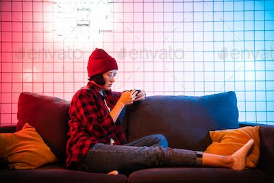 Woman sit on sofa and play mobile game happily at home