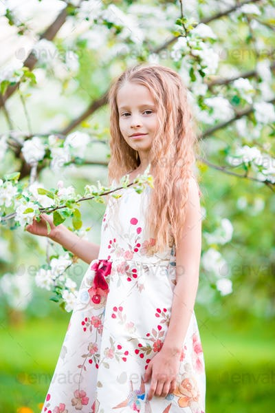 Portrait of little girl in blooming apple tree garden on spring day