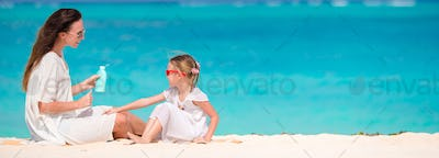 Young mother applying sun cream to daughter nose on bach vacation in hot day
