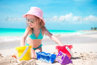 Cute little girl playing with beach toys on the seashore
