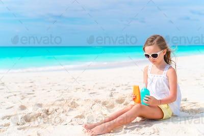 Little adorable girl with suncream bottle on the beach