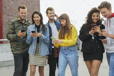 Young people using their smart phones in a row