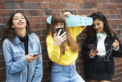 Three young women having fun with mobile phone