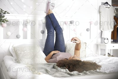 Teenage girl lying on the bed and making a selfie