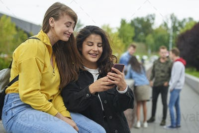 Happy girls looking at smart phone