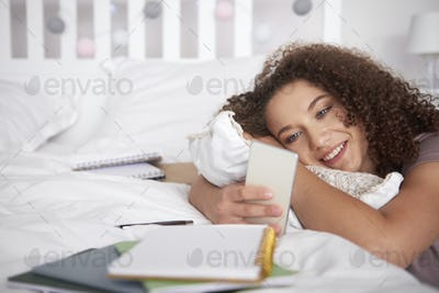 Smiling teenage girl using a smart phone in her room