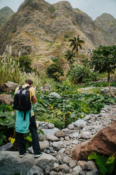 Male photographer in verdant valley covered with lotus plants. Santo Antao Cape Verde