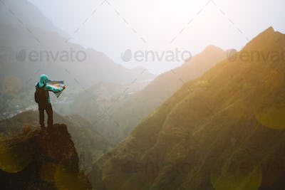 Man with the map staying on top of the mountain rock with gorgeous panorama view over high mountain