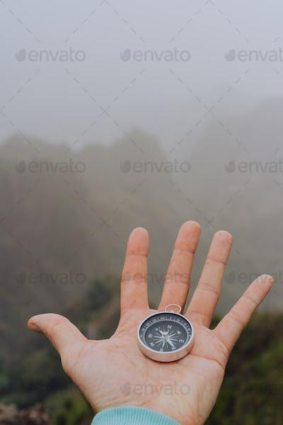 Man palm holding compass. Foggy mountainous landscape