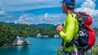 Traveler with Backpack enjoy the View over Roks in Kabui Bay near Waigeo. West Papuan, Raja Ampat