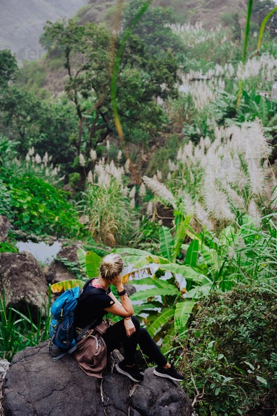 Girl resting after track on the stone and admiring spectacular green banana and sugarcane plants on