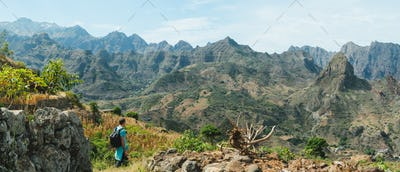 Man hiker walking among remote mountainous landscape with agriculture terraces in vertical valley