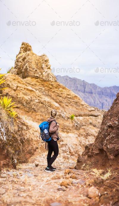 Woman hiker on the stony trekking trail in front of the barren mountain peak on Santo Antao island