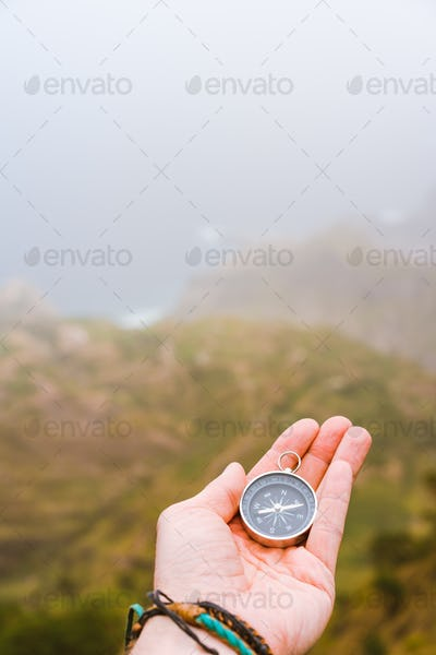 Palm with compass. Concept of figure out right direction. Haze valley and mountains in background