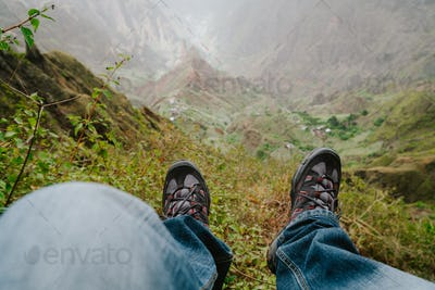 Feet with trekking footwear swing over the valley with mountain peak after long hike. Santo Antao