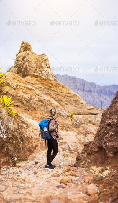 Woman hiker on the stony trekking trail in front of the barren mountain peak on Santo Antao island