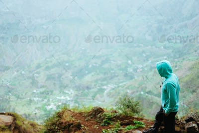 Traveler on the mountain edge overlooking the rural landscape of Paul valley. Santo Antao Island