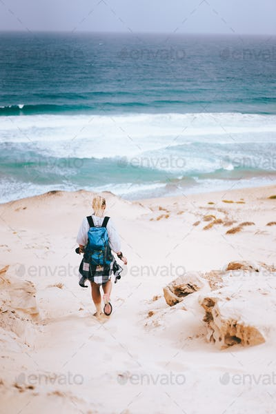 Woman hiker with backpack going down a sand dune towards the lonely beach. Sao Vicente Cape Verde