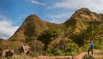 Panoramic view of woman tourist with blue backpack making photo of landscape in Mountains of Santo