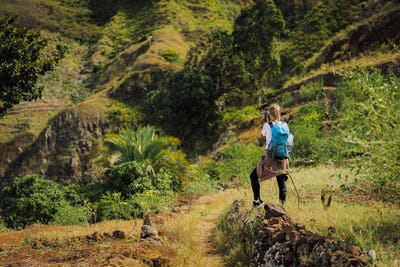 Woman tourist with blue backpack making photo of landscape in Mountains of Santo Antao island, Cabo