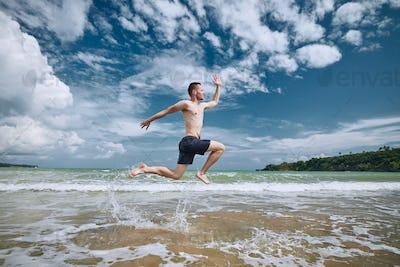 Joyful man jumping on beach
