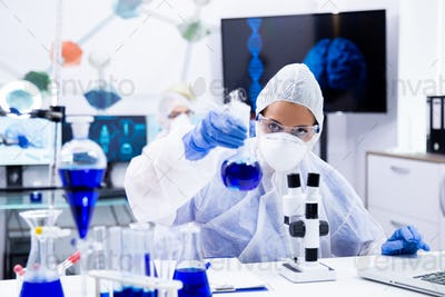 Female scientist in protection equipment holding and looking at a test tube with blue solution