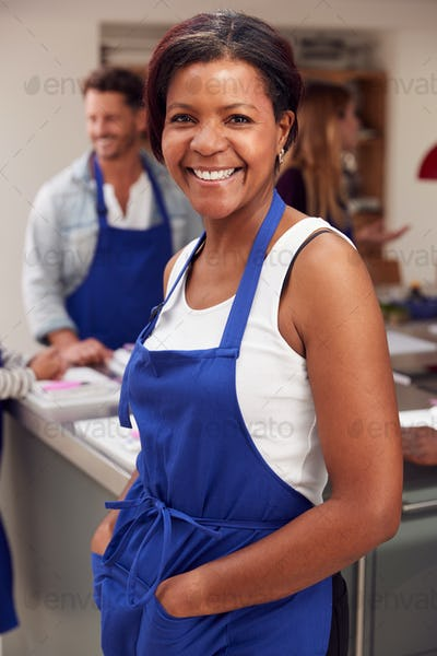 Portrait Of Smiling Mature Woman Wearing Apron Taking Part In Cookery Class In Kitchen