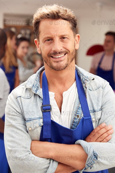 Portrait Of Smiling Mature Man Wearing Apron Taking Part In Cookery Class In Kitchen
