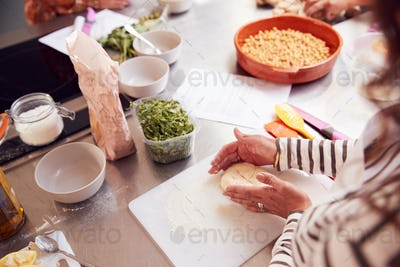 Close Up Of Female Teacher Demonstrating How To Use Dough To Make Flatbread In Cookery Class