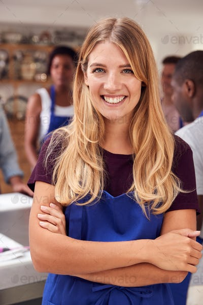 Portrait Of Smiling Woman Wearing Apron Taking Part In Cookery Class In Kitchen
