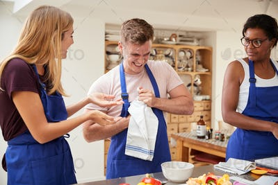 Man Struggling To Open Bottle As Students Prepare Ingredients For Dish In Kitchen Cookery Class