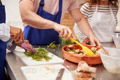 Close Up Of Male And Female Adult Students Preparing Ingredients For Dish In Kitchen Cookery Class