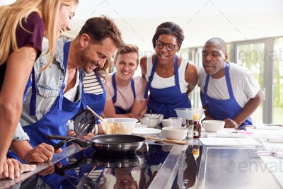 Male Teacher Making Pancake On Cooker In Cookery Class As Adult Students Look On