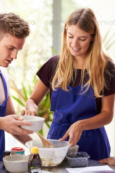 Female Teacher With Male Student Mixing Ingredients For Recipe In Cookery Class In Kitchen