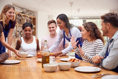 Group Of Men And Women Sitting Around Table Eating Meal They Have Prepared In Kitchen Cookery Class