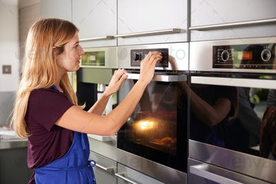 Woman Wearing Apron In Kitchen Checking On Peppers Roasting In Oven Taking Part In Cookery Class