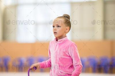 Adorable little girl athletes train in rhythmic gymnastics hall