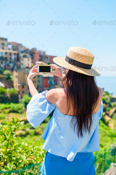 Young woman take a photo of beautiful view at old village in Cinque Terre, Liguria, Italy. European
