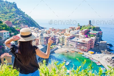Young girl with small toy model airplane background of beautiful Vernazza