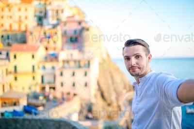 Young man taking selfie background beautiful Manarola village, Cinque Terre, Liguria, Italy