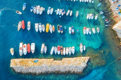 Aerial view of colorful boats and yachts in port in blue sea