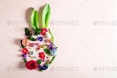 Easter minimal concept. Egg shape with bunny ears made from flowers