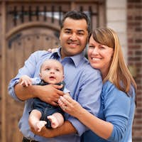 Happy Mixed Race Couple with Baby in Front of House