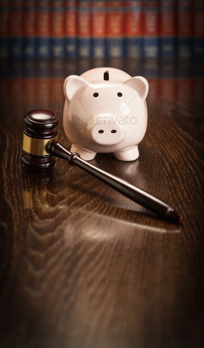 Gavel and Piggy Bank on Wooden Table With Law Books In Background