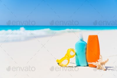 Suncream bottles, goggles, starfish on white sand beach background ocean