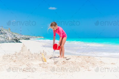 Little girls play with beach toys during tropical vacation